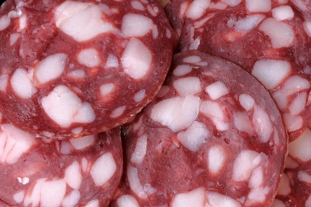 Rohe geräucherte wurst geschnitten in dünne scheiben lebensmittelfleischhintergrund