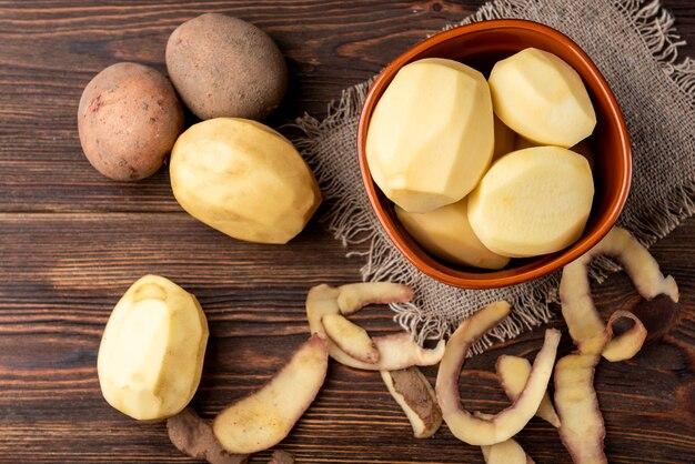 Rohe geschälte kartoffeln in der schüssel auf dunkler holzoberfläche.