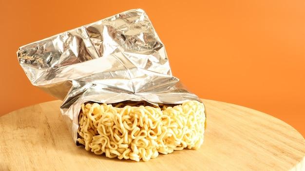 Rohe getrocknete instantnudeln auf einem runden hölzernen schneidebrett in einer folienverpackung auf gelbem grund.