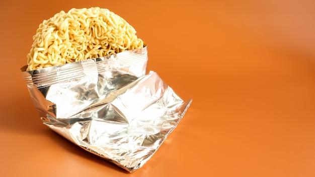 Rohe getrocknete instantnudeln in offenem zustand aus einer unbenannten folienverpackung ohne namensnahaufnahme auf gelbem grund. nudeln, für deren zubereitung es ausreicht, wasser zu gießen.