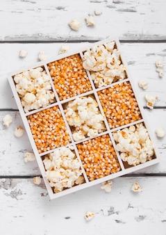 Rohe goldene zuckermais-samen und popcorn in der weißen holzkiste auf hellem hintergrund