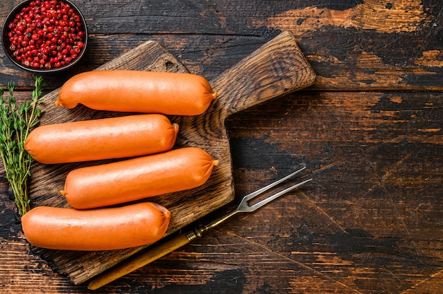 Rohe grillwürste bratwurst aus schweinefleisch auf einem schneidebrett. dunkler hölzerner hintergrund. draufsicht. speicherplatz kopieren.