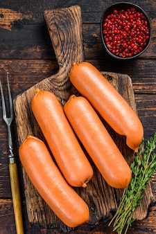 Rohe grillwürste bratwurst aus schweinefleisch auf einem schneidebrett.