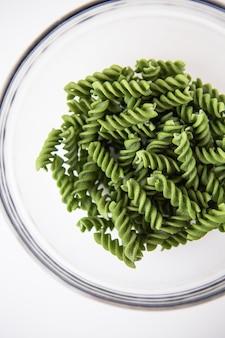 Rohe grüne fusilli-nudeln in einem transparenten teller, natürlich auf basis von spinat und spirulina. leckeres und gesundes essen. nahaufnahme.