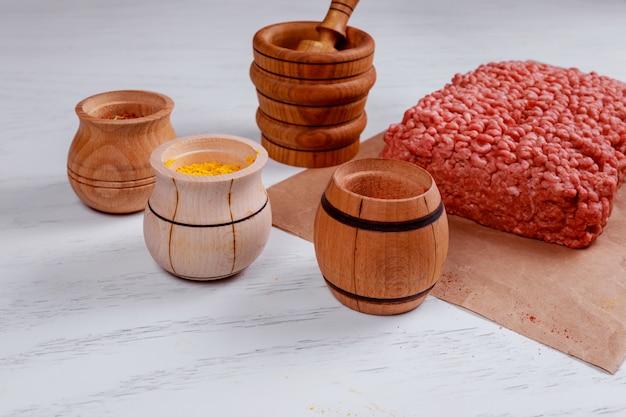 Rohe hackfleischzutaten auf papier mit zwiebeln, kräutern und spargeln