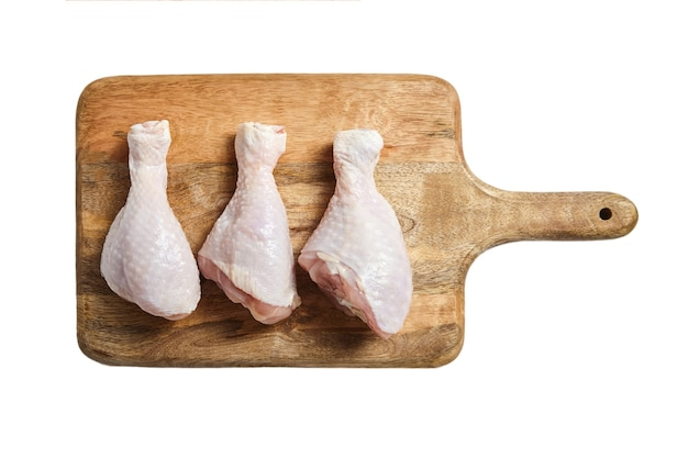 Rohe hähnchenschenkel auf einem hölzernen schneidebrett. ungekochtes fleisch lokalisiert auf weißem hintergrund. draufsicht