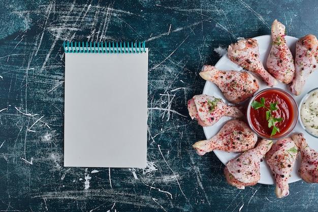 Rohe hähnchenschenkel auf einer weißen platte mit einem rezeptbuch beiseite.