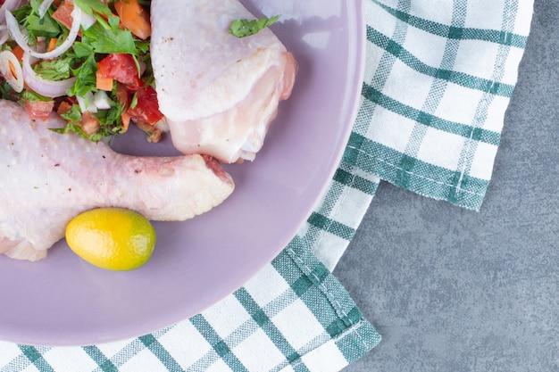 Rohe hähnchenschenkel mit gemüse auf lila platte.