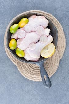 Rohe hähnchenschenkel mit gemüse in schwarzer pfanne.