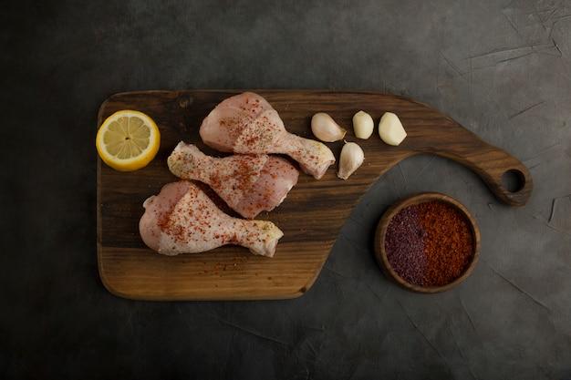 Rohe hähnchenschenkel serviert mit zitrone und gewürzen