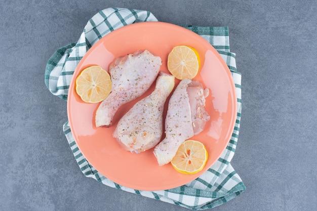 Rohe hähnchenschenkel und zitronen auf orangenteller.