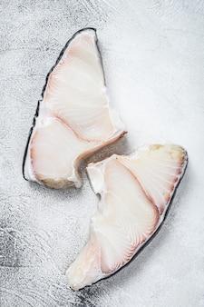 Rohe haifischsteaks auf einem küchentisch auf weiß. draufsicht.