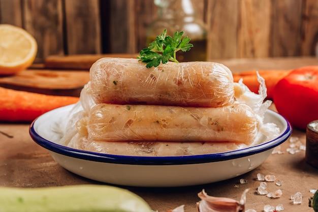 Rohe hausgemachte hühnerwurst auf rustikalem hintergrund. diät-gesundes lebensmittelkonzept. selektiver fokus