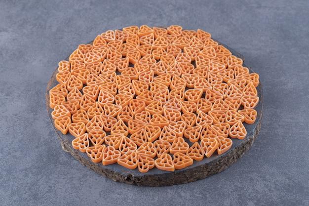 Rohe herzförmige nudeln auf holzstück.