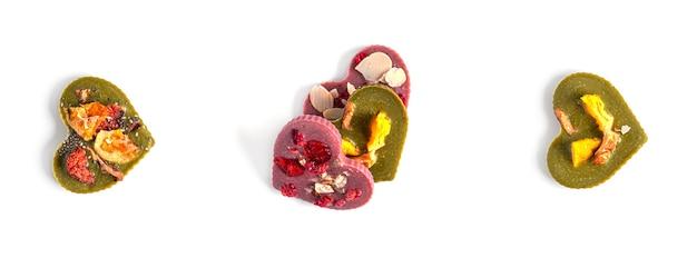 Rohe herzförmige schokolade mit getrockneten früchten und nüssen auf einem weißen hintergrund. hochwertiges foto
