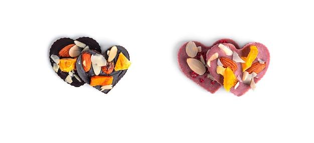 Rohe herzförmige schokolade mit getrockneten früchten und nüssen auf einem weißen hintergrund