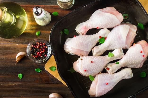 Rohe hühnerbeine in einer bratpfanne auf einem holztisch. fleischzutaten zum kochen. draufsicht