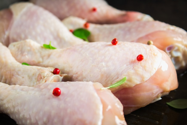 Rohe hühnerbeine in einer bratpfanne auf einem holztisch. fleischzutaten zum kochen.