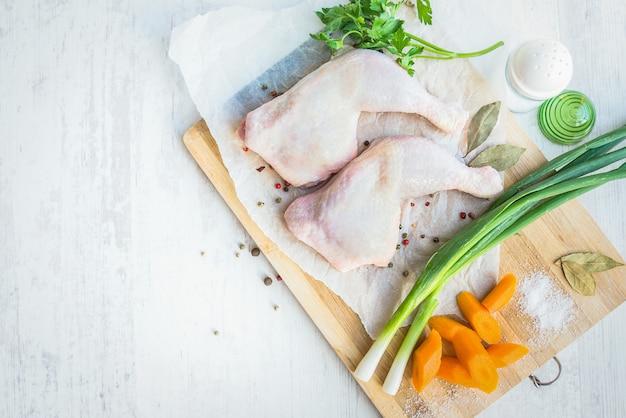 Rohe hühnerbeine mit gemüse und gewürzen