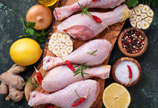 Rohe hühnerbeine mit gewürzen und knoblauch.