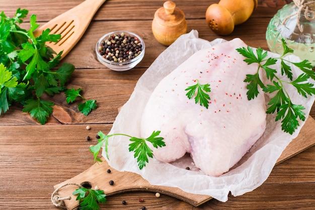 Rohe hühnerbrust auf einem rahmen in den gewürzen und in den kräutern auf einem schneidebrett auf einem holztisch