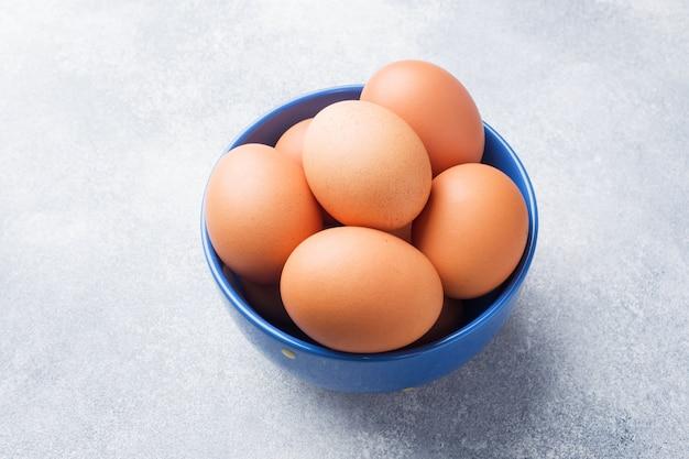 Rohe hühnereien browns in einer blauen schüssel auf einem grauen hintergrund.