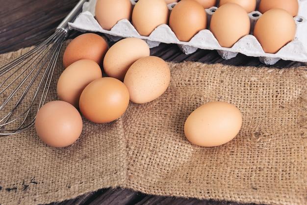 Rohe hühnereier auf sackleinenstoff auf altem braunem holz