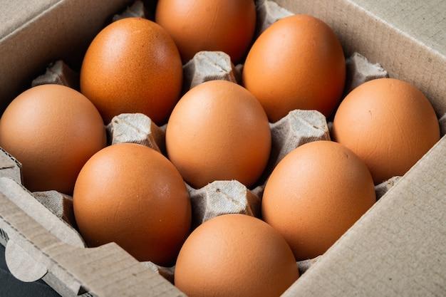 Rohe hühnereier im eierkartonsatz, auf schwarzem hintergrund