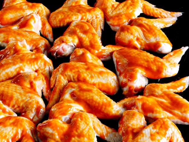 Rohe hühnerflügel in der heißen roten soße auf einem backblech bevor dem backen.