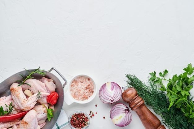 Rohe hühnerflügel in einer weißen schüssel mit gewürzen und zutaten zum kochen auf hellem schiefer-, stein- oder betonhintergrund. draufsicht mit kopienraum. attrappe, lehrmodell, simulation.