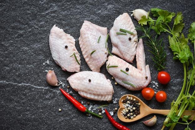 Rohe hühnerflügel, kräuter und gewürze mit pfeffer-chili-tomaten-knoblauch zum kochen, rosmarin-huhn