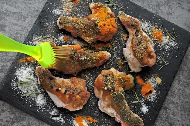 Rohe hühnerflügel mariniert in gewürzen auf einem schwarzen steinbrett.