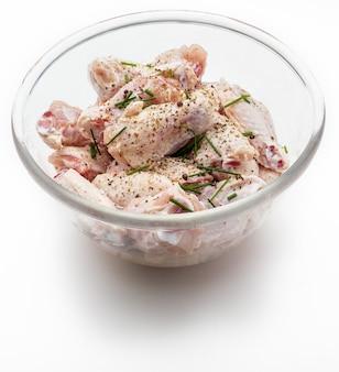 Rohe hühnerflügel mariniert mit salz, pfeffer und schnittlauch in einer schüssel lokalisiert auf weißem hintergrund.