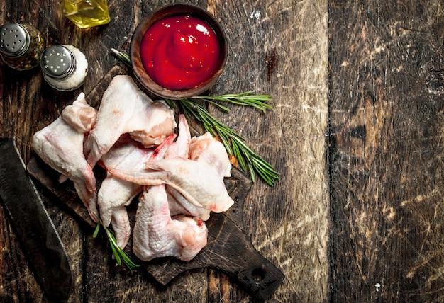 Rohe hühnerflügel mit tomatensauce und kräutern. auf einem holztisch.
