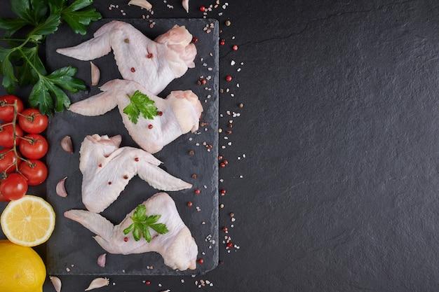 Rohe hühnerflügel mit zutaten zum kochen. rohes fleisch. hühnerflügel liegen auf einem holzbrett mit gemüse und gewürzen auf einem schwarzen hintergrund.