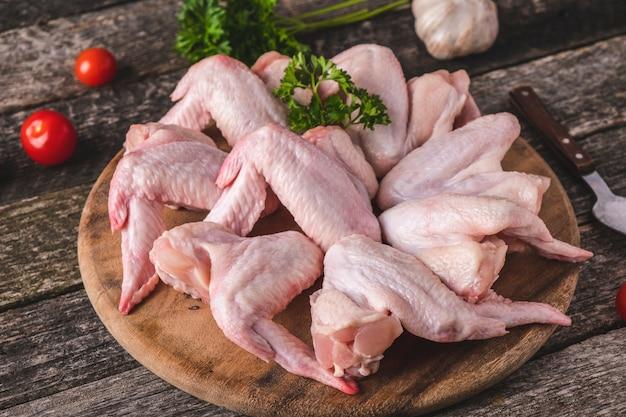 Rohe hühnerflügel mit zutaten zum kochen.