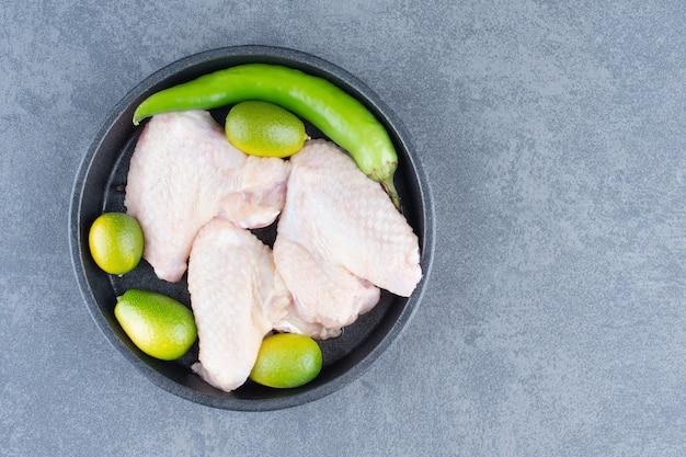 Rohe hühnerflügel und chili-pfeffer auf schwarzem teller.