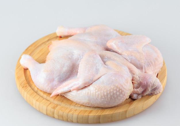 Rohe hühnerkarkasse auf dem schneidebrett lokalisiert auf weiß