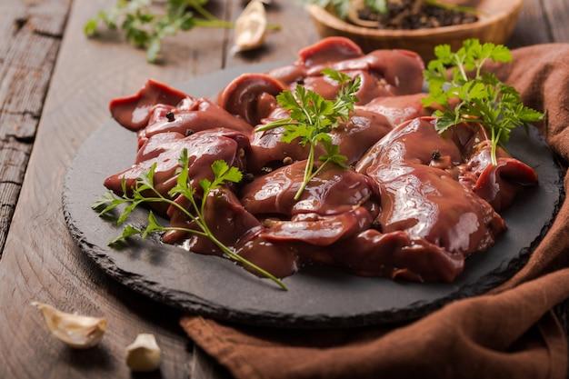 Rohe hühnerleber, garniert mit petersilie und pfeffer