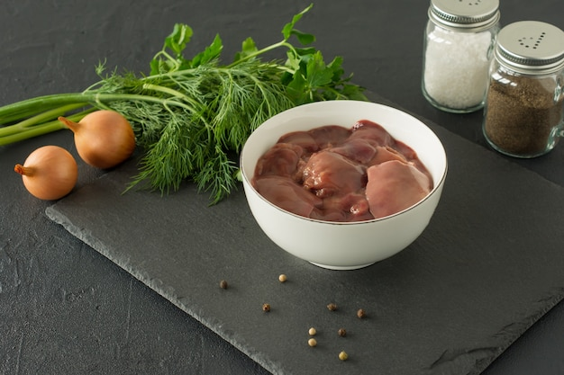 Rohe hühnerleber in schüssel auf schwarz zutaten zum kochen.
