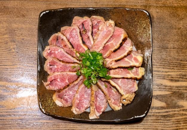 Rohe hühnerrippe, die auf keramischer platte auf tabelle sich vorbereitet