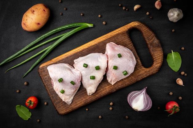 Rohe hühnerschenkel mit frühlingszwiebeln auf schwarzem hintergrund.