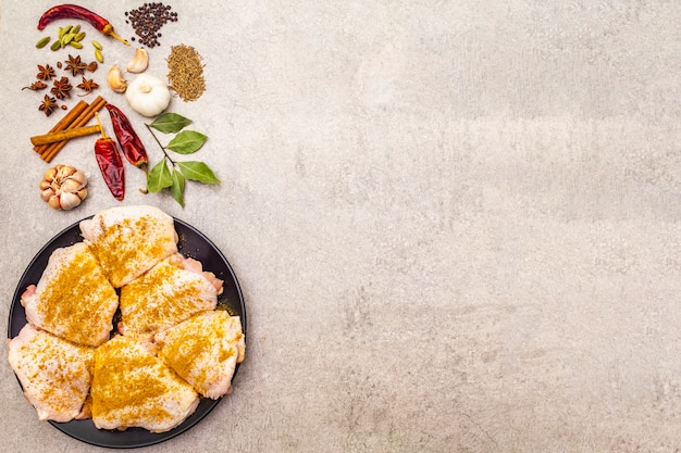 Rohe hühnerschenkel mit traditionellen indischen gewürzen. gelbe currymischung, sternanis, kardamom, lorbeerblatt, pfeffer, knoblauch, zimt. zutaten zum kochen auf einer steinoberfläche, kopieren raum.