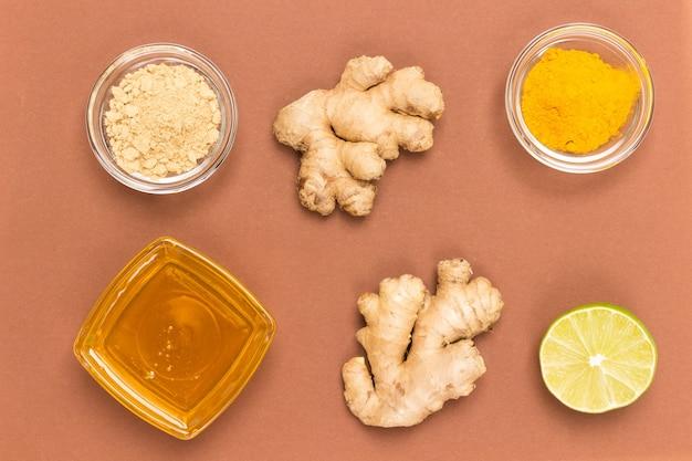 Rohe ingwerwurzel und trockener ingwer auf brauner oberfläche mit honig in einer glasschüssel