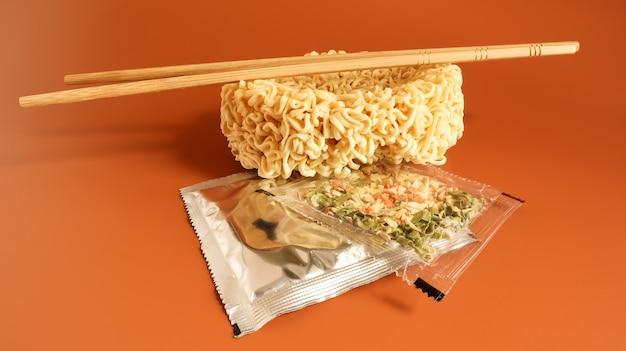 Rohe instantnudeln mit stäbchen und gewürzen. kopieren sie asiatisches essen des weltraums. nudeln, für deren zubereitung es ausreicht, kochendes wasser zu gießen und einige minuten zu warten. aromatisierte spaghetti.