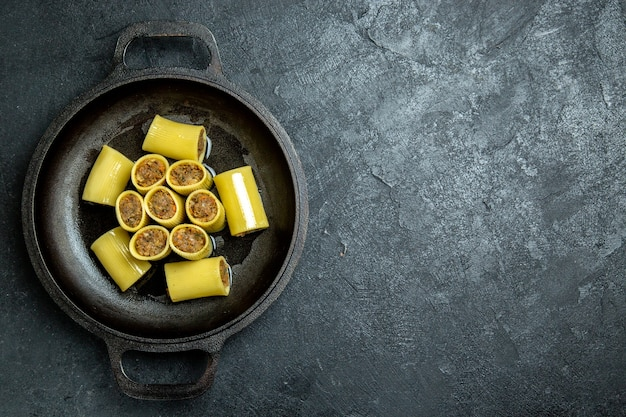 Rohe italienische nudeln der draufsicht mit fleisch innerhalb der pfanne auf dem rohen teigmehlnudelnahrungsmittel des dunklen hintergrunds