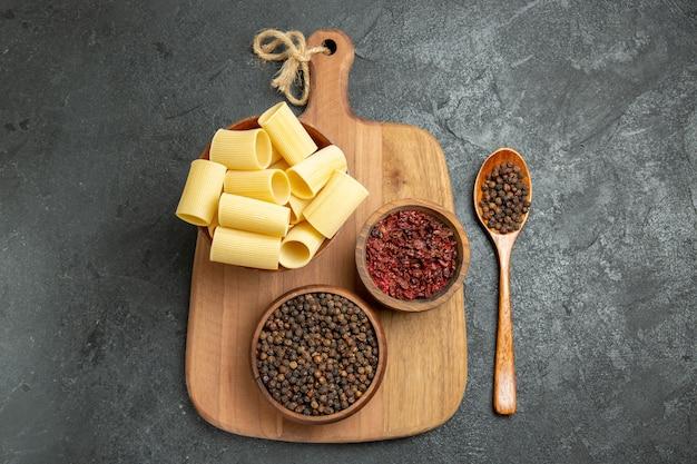 Rohe italienische nudeln der draufsicht mit gewürzen auf dem würzigen nudelteigmehl des grauen hintergrundnahrungsmittels würzig