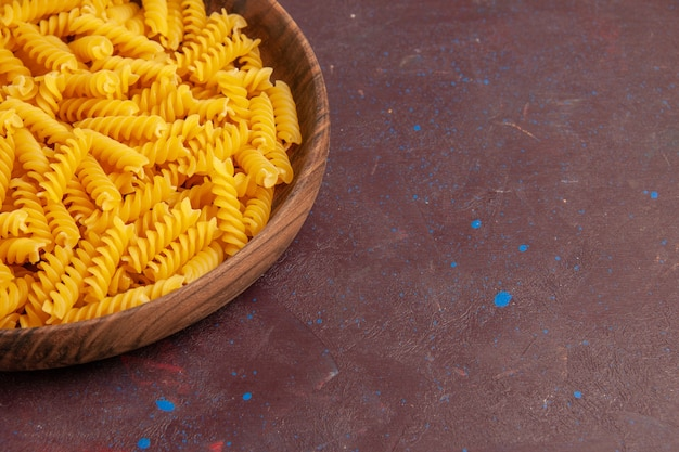 Rohe italienische nudeln der vorderansichtansicht innerhalb des holztabletts auf dunklem raum