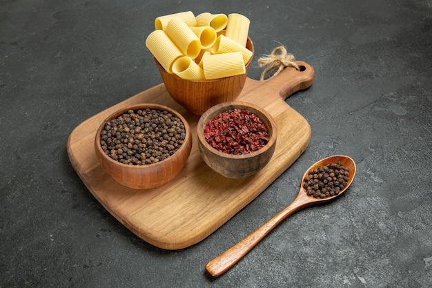 Rohe italienische pasta der vorderansicht mit gewürzen