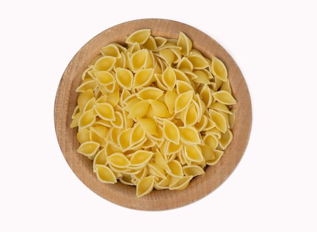Rohe italienische pasta in holzschale isoliert auf weißem hintergrund, ansicht von oben